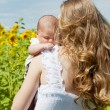 Young mother with the baby among blossoming sunflowers — Stock Photo