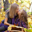 Happy mum and the daughter play autumn park on the fallen down foliage — Stock Photo #12572557