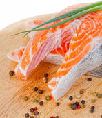 Stakes from a salmon with green onions and spices on a chopping board — Stock Photo