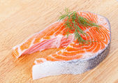Stake from a salmon on a wooden chopping board — Stock Photo