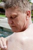 男人穿上皮肤防护霜从太阳 — 图库照片