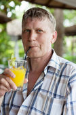 Man drinks orange juice in summer cafe — Stock Photo