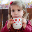 Little girl drinks milk from a big mug — Stock Photo #13579660