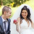 Bride treats the groom with a ripe peach - Stock Photo