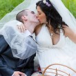 Groom and the bride together sit on a grass with a big basket of fruit and kiss — Stock Photo
