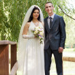 Stock Photo: Groom and the bride cost on the wooden bridge in a summer garden
