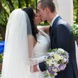 Newly-married couple kiss after ceremony of wedding - Stockfoto