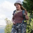Female hiker with backpack in grass at mountains — Stock Photo