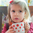 Little girl drinks milk from a big mug — Stock Photo