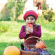 Little girl sits on a grass near to a basket with vegetables and eats carrots — Stock Photo