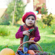 Little girl sits on a grass near to a basket with vegetables and eats carrots — Stock Photo #13579670