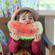 Little girl in a straw hat with appetite eats a ripe water-melon — Stock Photo #13579671