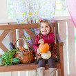 Little girl sits on a bench on a terrace with a basket with vegetables — Stock Photo