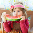 Little girl in a straw hat with appetite eats a ripe water-melon — Stock Photo #13579674