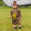 Little girl in a military uniform against planes — Foto Stock