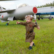 Little girl in a military uniform against planes — Stockfoto