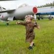 niña en un uniforme militar contra aviones — Foto de Stock