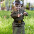 Little girl in a military uniform against planes — Stok fotoğraf