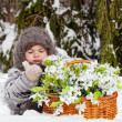 Little girl in a winter wood with the big basket of snowdrops — Stock Photo #13579698
