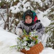 Little girl in a winter wood with the big basket of snowdrops — Stock Photo #13579704