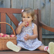 Little girl sits on a bench with a basket of apples — Stock Photo #13579705