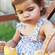 Little girl eats a juicy pear — Stock Photo