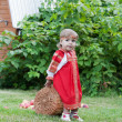 Little girl in a traditional Russian national sundress bears a heavy basket with apples — Stockfoto