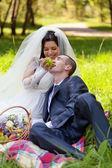 Glad brud behandlar brudgummen med druvor — Stockfoto