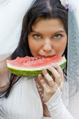 Beautiful bride eats a juicy water-melon, a close up — Stock Photo