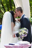 Newly-married couple kiss after ceremony of wedding — Stock Photo