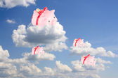 Pigs-coin boxes sit on white clouds in the blue sky — Stock Photo