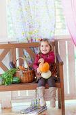 Liten flicka sitter på en bänk på en terrass med en korg med grönsaker — Stockfoto