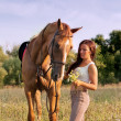 Young girl and horse on a summer meadow — Stock Photo #14080458