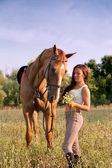 Young girl and horse on a summer meadow — Stock Photo