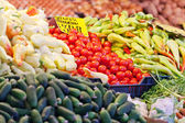 Tomatoes and other vegetables on a supermarket counter — Stock Photo