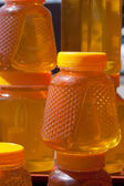 Jugs with honey on a counter in the market — Stock Photo