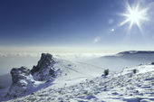 Beautiful landscape with snow-covered mountains, the sun and clouds — 图库照片
