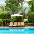 Chaise lounges at pool in hotel in tropics — Stock Photo