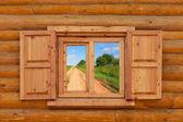 Camino rural es visible desde una ventana en la casa rural de madera — Foto de Stock