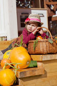 Child in a straw hat sits on wooden steps with pumpkins — Stock Photo