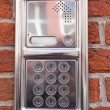 Stock Photo: Metal on-door speakerphone on brick wall