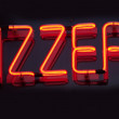 "Stock Photo: Being shone inscription ""Pizzeria"" on black background"
