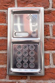 Metal on-door speakerphone on a brick wall — Stock Photo