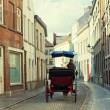 Tourists in a phaeton go on ancient streets of Bruges, Belgium - Stock Photo
