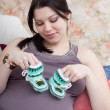 Happy pregnant woman chooses children's things, sitting on a sofa - Stock Photo