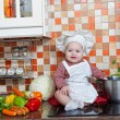 Baby cook with vegetables sits in a wattled basket on a kitchen table — Stock Photo