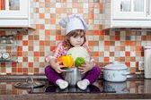 Ragazza cuoco con verdure fresche si siede su un tavolo da cucina — Foto Stock