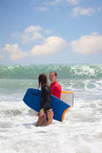 Man and the girl with a surfboard go on an ocean coast — Stock Photo