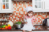 Girl in a cook cap with a ladle in a hand sits on a kitchen table — Stock Photo