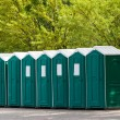 Green plastic toilet booths in park - Stock Photo
